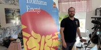 Kenneth står vid sitt skrivbord med Trollhättan Energi-backdropp bakom