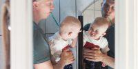 Pappa och bebis borstar tänderna och tittar sig i spegeln