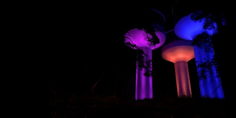 Belysta vattentorn i rosa, orange och blå på natten