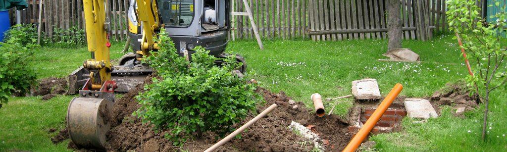 Grävmaskin som gräver i en trädgård