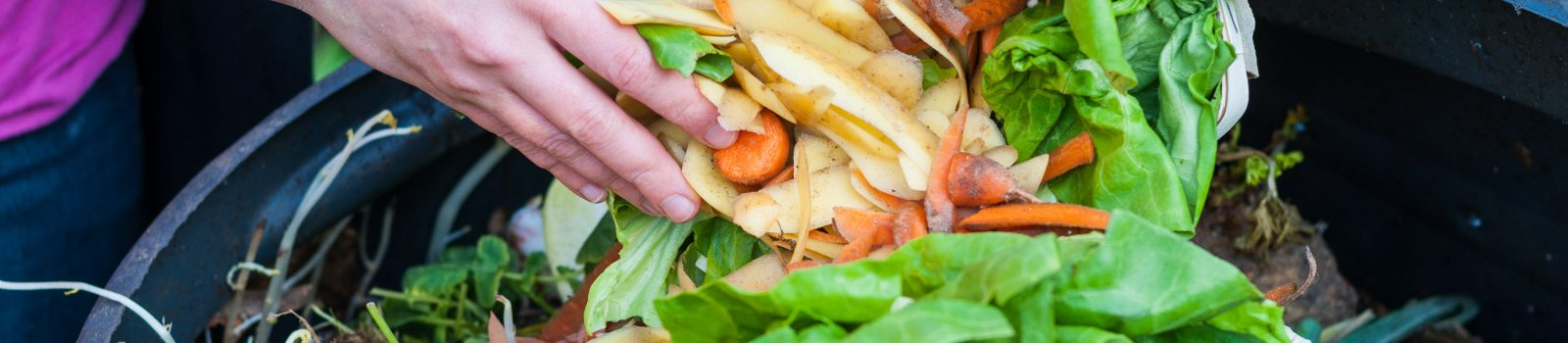 Tjej slänger matrester i komposttunna